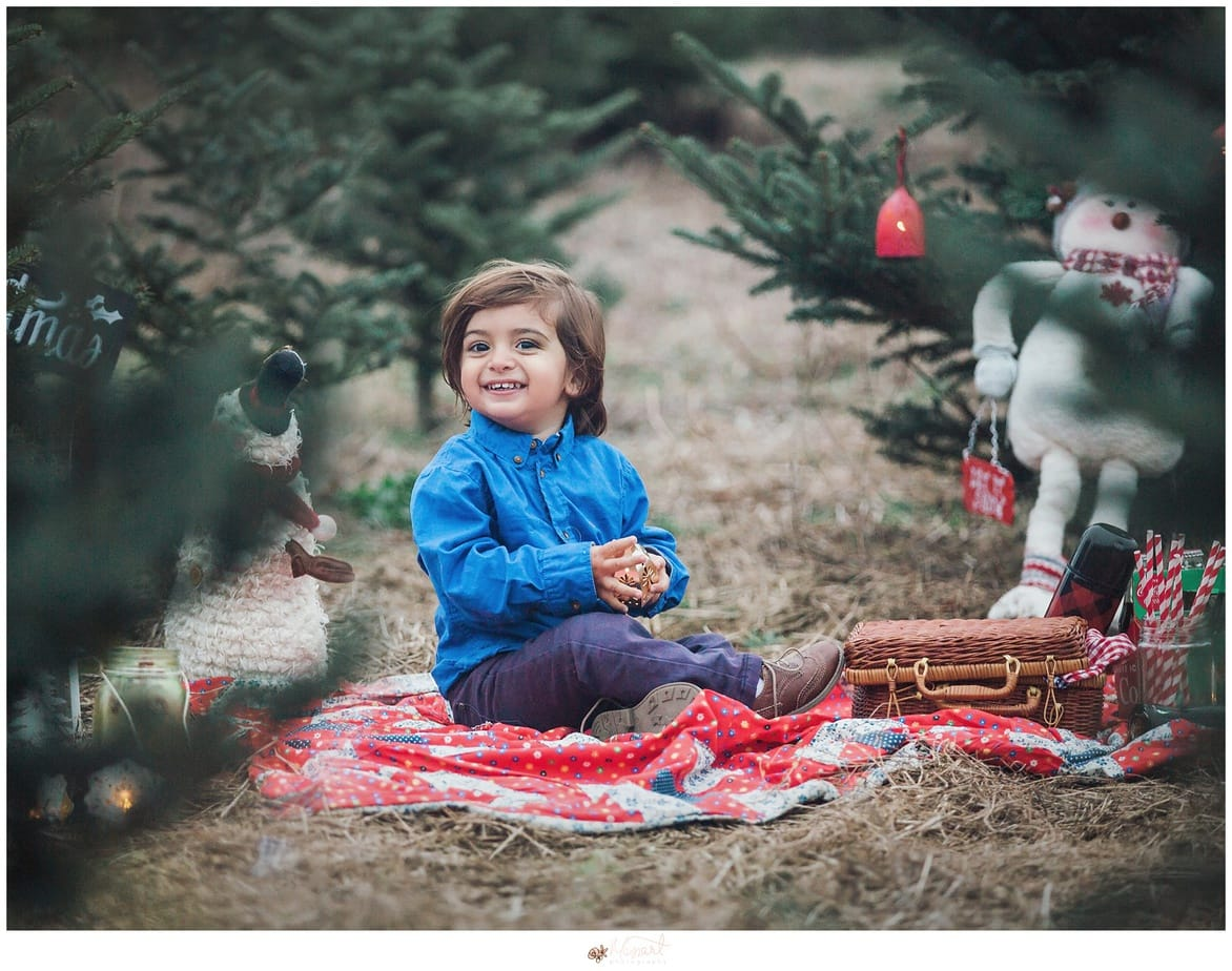 a holiday portrait of a little boy sitting in a christmas tree farm with snowmen and vintage quilt during his family holiday photography session with rhode island photographers of massart photography RI, CT, MA