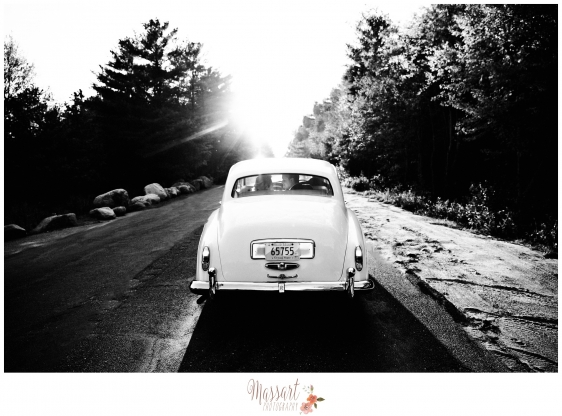 Black and white outdoor photo of bride and groom riding away in vintage car photographed by Massart Photography RI MA CT