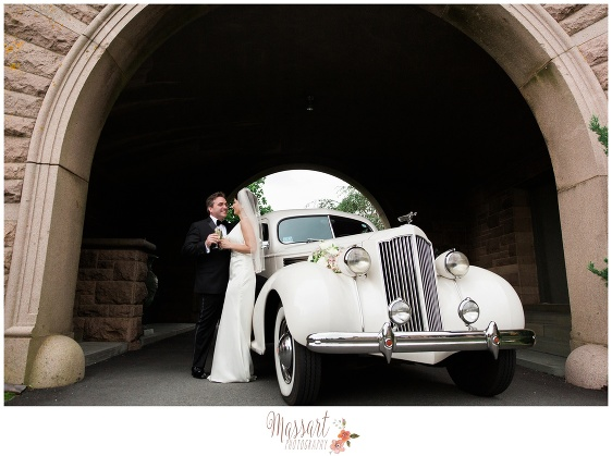 Portrait of bride and groom with antique Packard car under archway at Oceancliff Resort in Newport Rhode Island photographed by Massart Photography RI MA CT