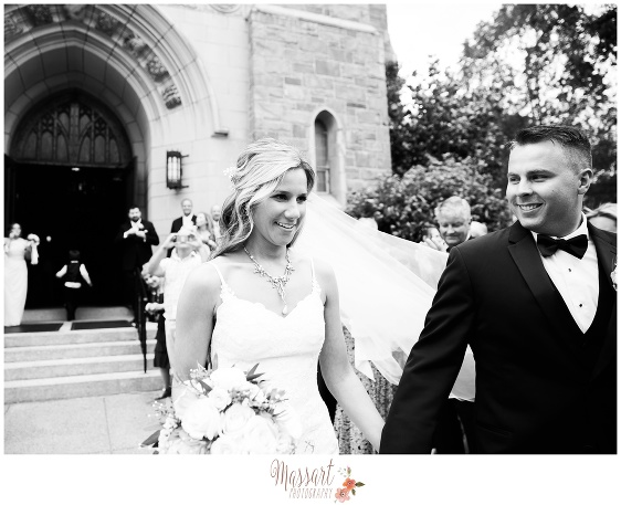 Black and white outdoor picture of bride and groom exiting the church after wedding ceremony captured by Rhode Island photographer of Massart Photography RI MA CT