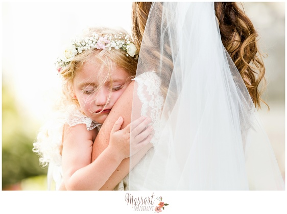 Picture of flower girl hugging bride photographed by Massart Photography of Warwick RI