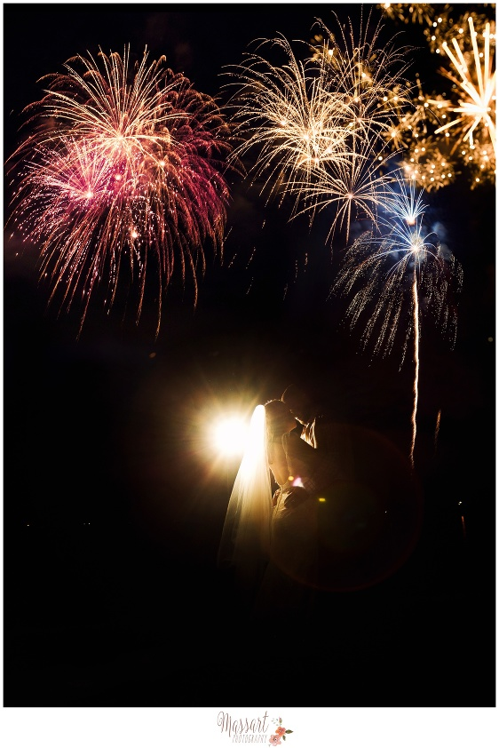 Portrait of bride and groom kissing with fireworks in the background photographed by Rhode Island photographers of Massart Photography RI MA CT