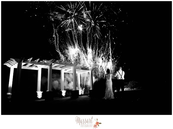 Outdoor black and white photograph of bride and groom watching wedding reception fireworks taken by Massart Photography of Warwick RI
