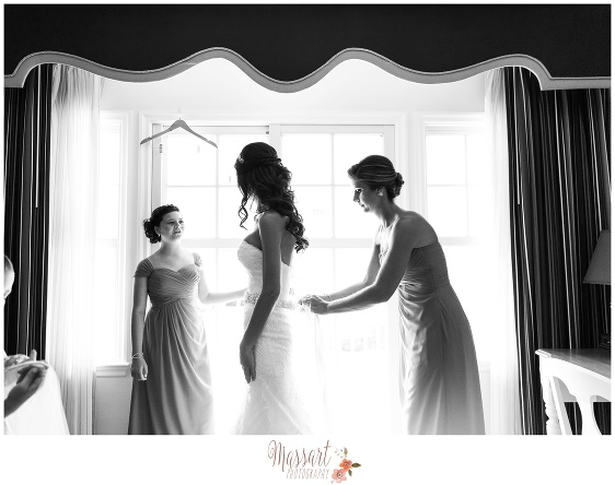 Black and white portrait of bride and bridesmaids in front of window putting on the wedding gown photographed by Massart Photography of Warwick Rhode Island