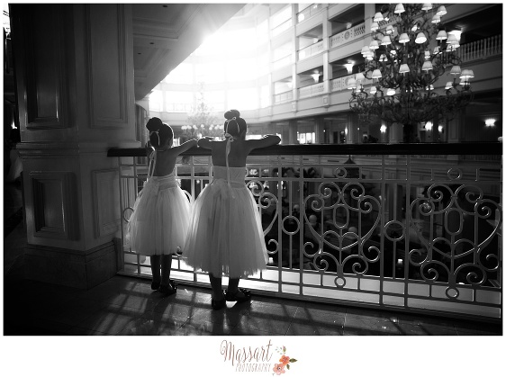 Black and white portrait of flower girls looking over the balcony inside the Grand Floridian Resort at Walt Disney World in Orlando FL taken by Massart Photography RI MA CT