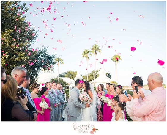 Celebratory photo of bride and groom kissing after ceremony as guests throw confetti photographed by Massart Photography RI MA CT
