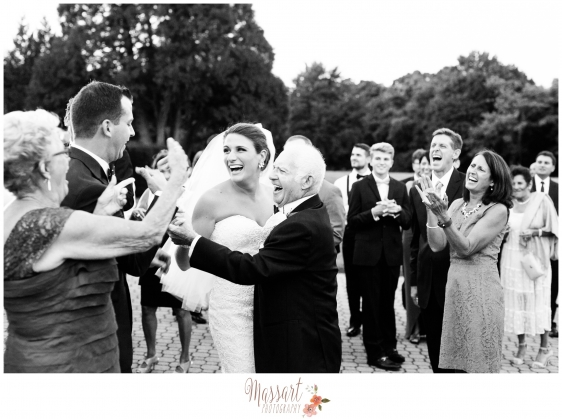 Black and white outdoor portrait of bride and groom laughing with guests by Massart Photography of Warwick Rhode Island