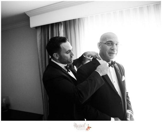 Black and white portrait of groom helping his father get ready before the wedding ceremony in Providence Rhode Island photographed by Warwick RI photographers of Massart Photography MA RI CT