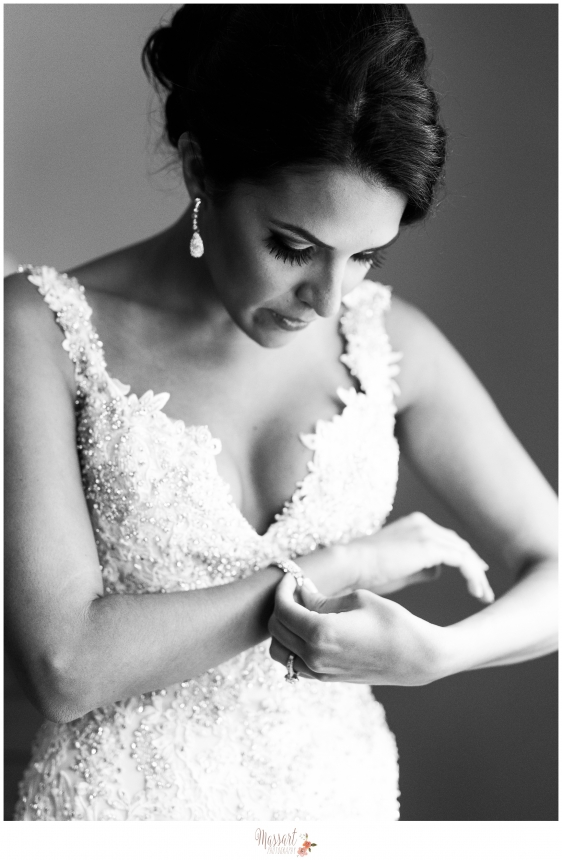 Black and white bridal portrait of bride in her wedding gown putting on jewelry on her wedding day photographed by Warwick Rhode Island photographer of Massart Photography RI MA CT