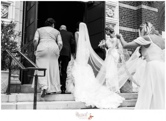 Black and white pic of bride and bridal party walking into church for wedding ceremony in Providence Rhode Island photographed by Warwick RI photographer of Massart Photography RI MA CT