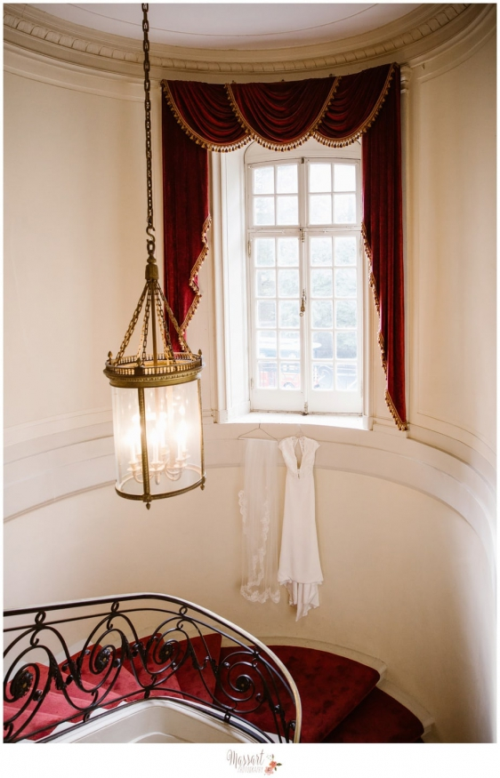 Wedding day portrait of veil and dress hanging in staircase at Glen Manor House in Rhode Island photographed by Massart Photography RI MA CT