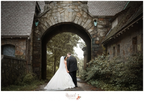 Outdoor wedding day portrait of bride and groom under the arch at Aldrich Mansion in Warwick RI taken by Rhode Island photographers of Massart Photography MA RI CT