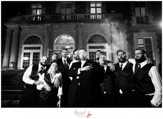 Black and white outdoor photo of groom and groomsmen with cigars at Aldrich Mansion in Warwick Rhode Island taken by Massart Photography MA CT RI