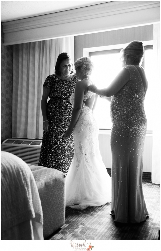 Black and white photo of mother of groom and grandmother of bride helping her get dress on taken by Warwick Rhode Island photographers of Massart Photography RI MA CT