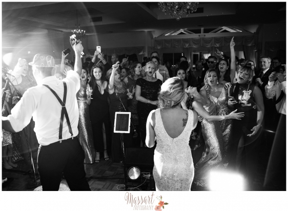 Black and white wedding portrait of bride and groom partying with their guests on their wedding day taken by Rhode Island photographers of Massart Photography RI MA CT