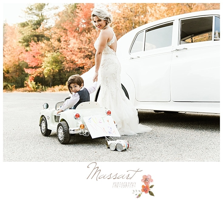 Wedding day portrait of bride and little boy with mini vintage car and antique Rolls Royce
