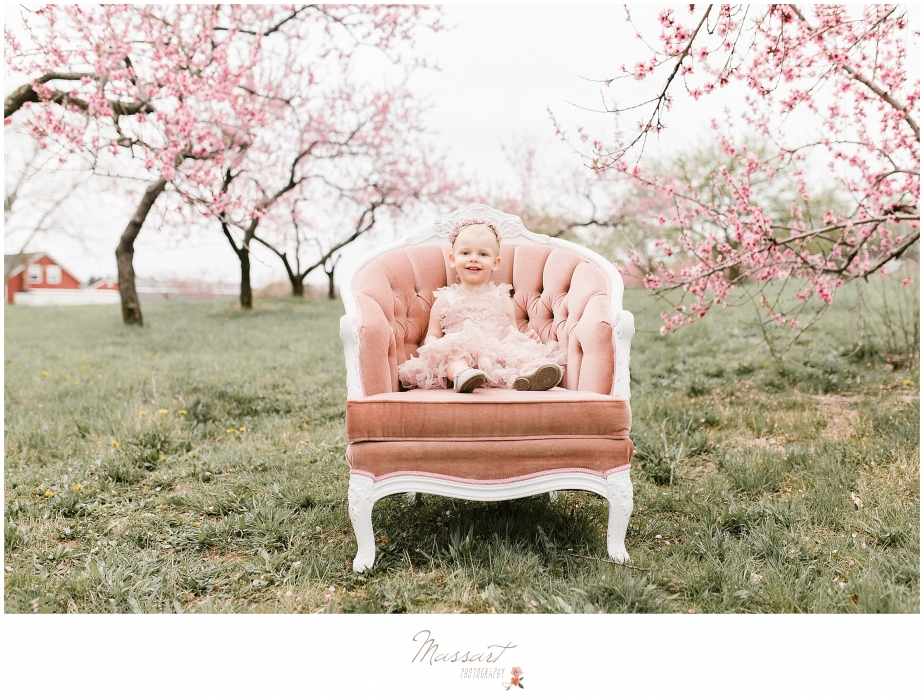Outdoor spring portrait of a little girl in a tutu sitting in a vintage chair photographed by Massart Photography, RI MA CT.