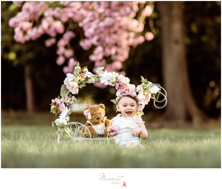 Outdoor spring family portrait of a baby playing in the flowers photographed by Massart Photography, RI MA CT.