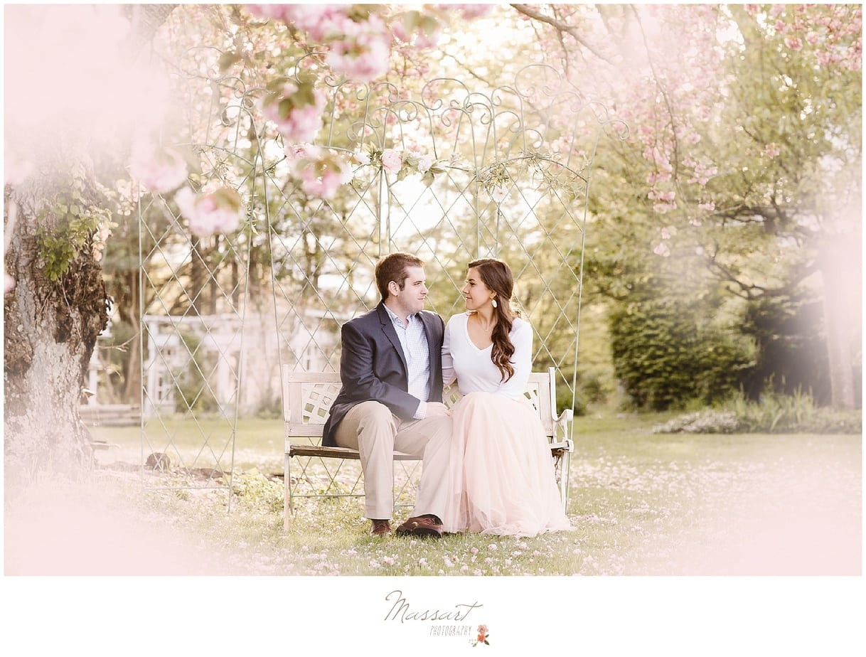 Spring engagement portrait session of couple sitting on a park bench photographed by Massart Photography of Warwick, Rhode Island.