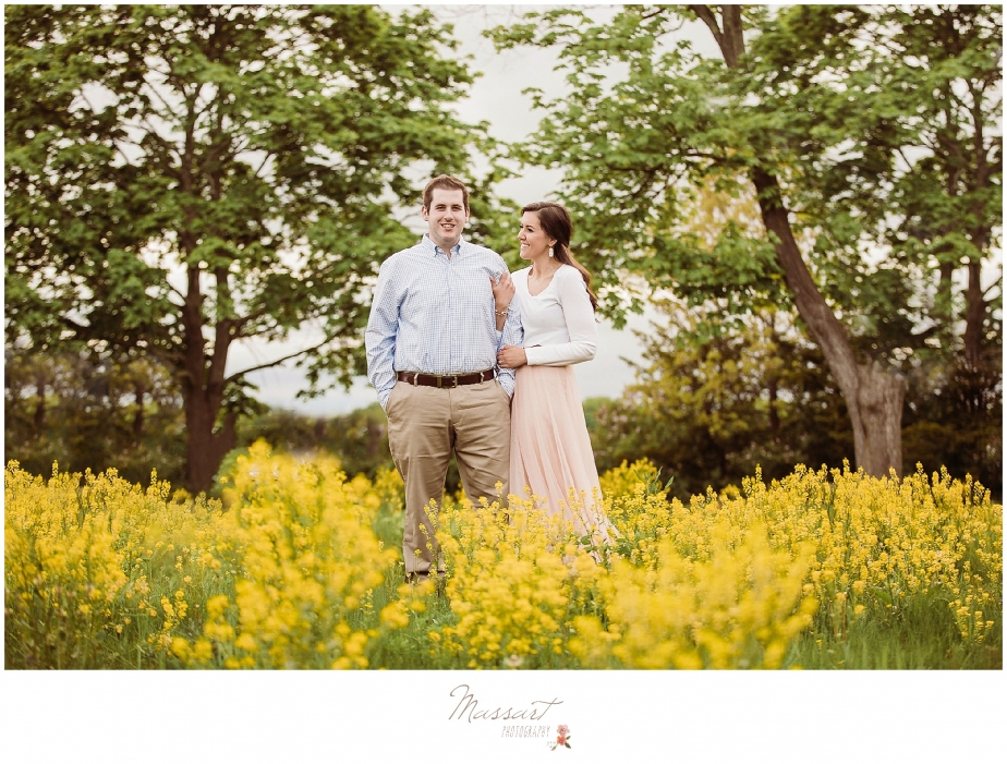 An engaged couple has a spring portrait session in a wildflower field photographed by Massart Photography of Warwick, Rhode Island.