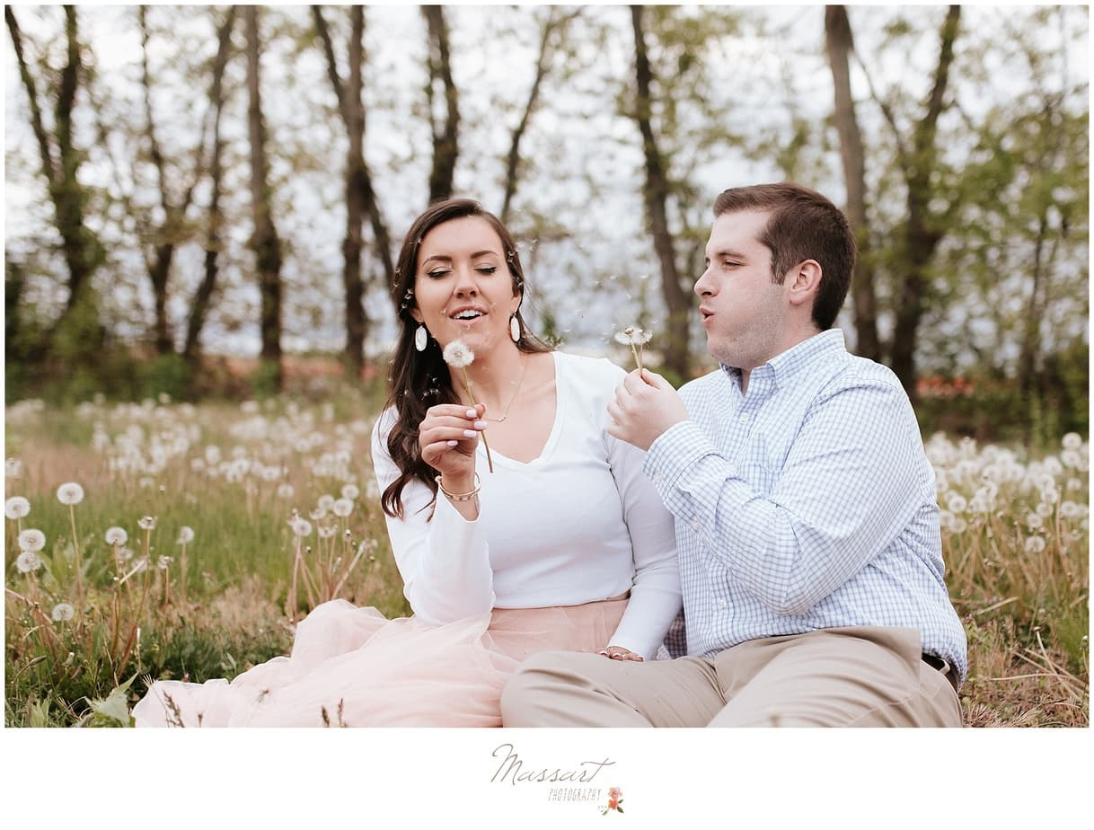 Spring engagement portrait in a field of dandelions photographed by Massart Photography of Warwick, Rhode Island.
