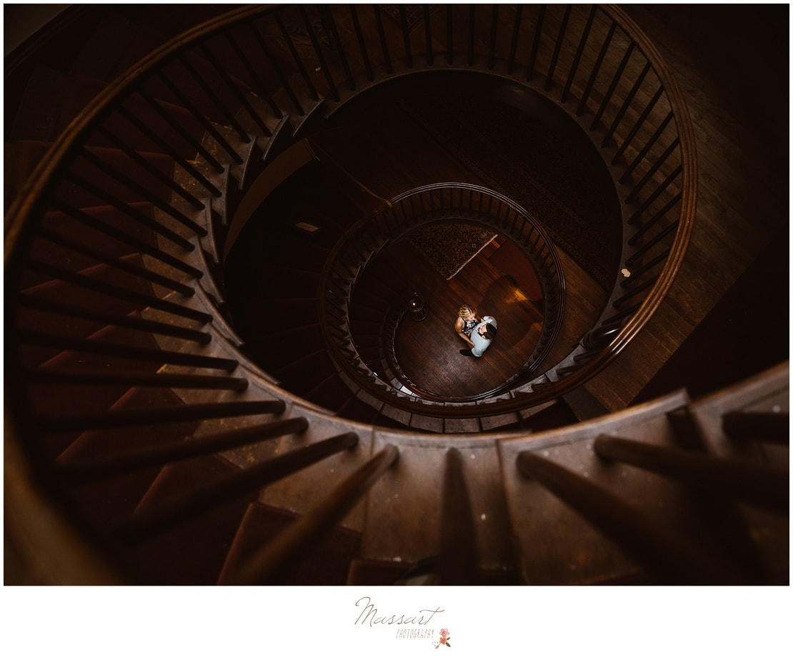 Engaged couple photographed at the bottom of a spiral staircase photographed by Massart Photography RI MA CT.