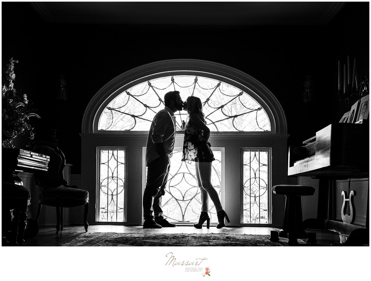 An engaged couple kisses in front of an arched window photographed by Massart Photography of Warwick, Rhode Island.