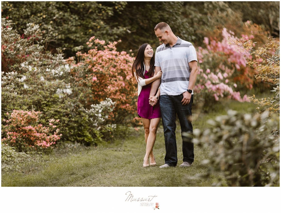 Outdoor engagement photo shoot of couple walking through a garden photographed by Massart Photography, RI MA CT
