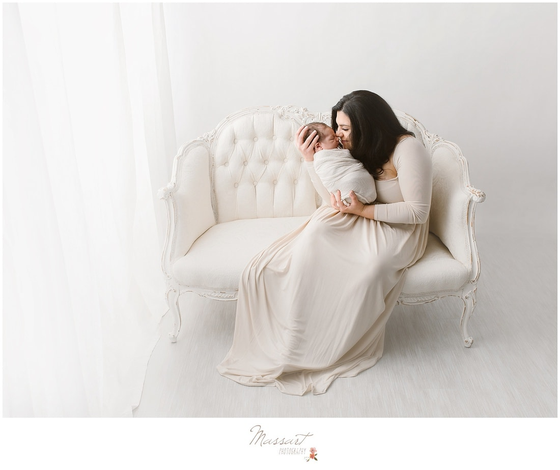 mother and newborn child photographed on a vintage couch by Massart Photography of Rhode Island