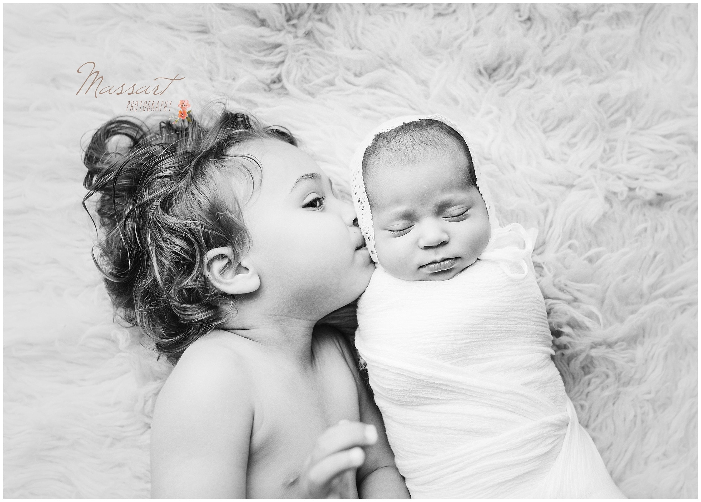 Big brother kisses his newborn baby sister photographed by Massart Photography of Warwick, Rhode Island