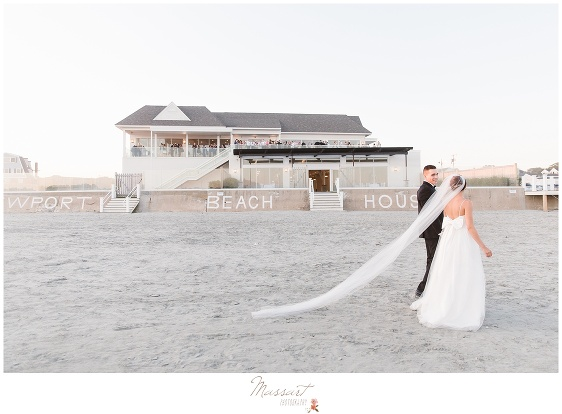 Bride and groom with the veil in the sand on the beach at the Newport Beach House wedding photographed by Massart Photography RI