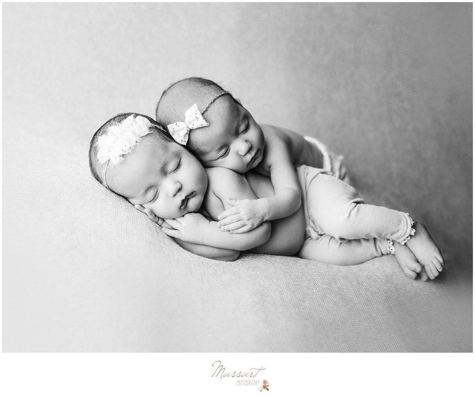 Newborn twin baby girls sleep together during newborn portrait session photographed by Massart Photography of Warwick, RI