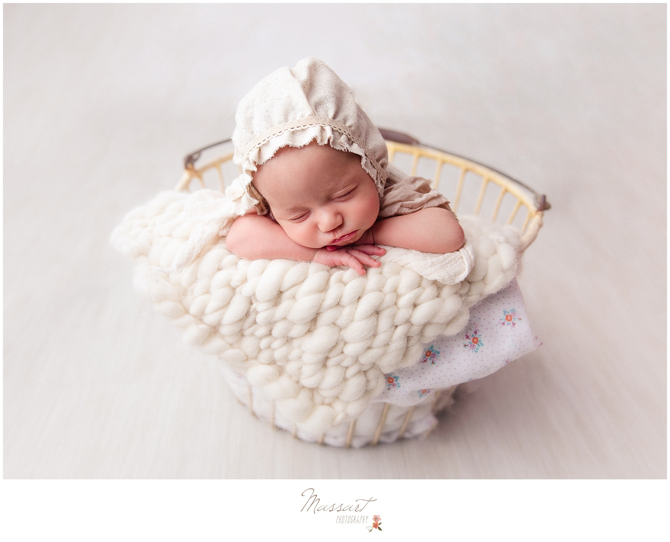 Newborn baby girl sleeps in a basket during newborn portrait session photographed by Massart Photography RI
