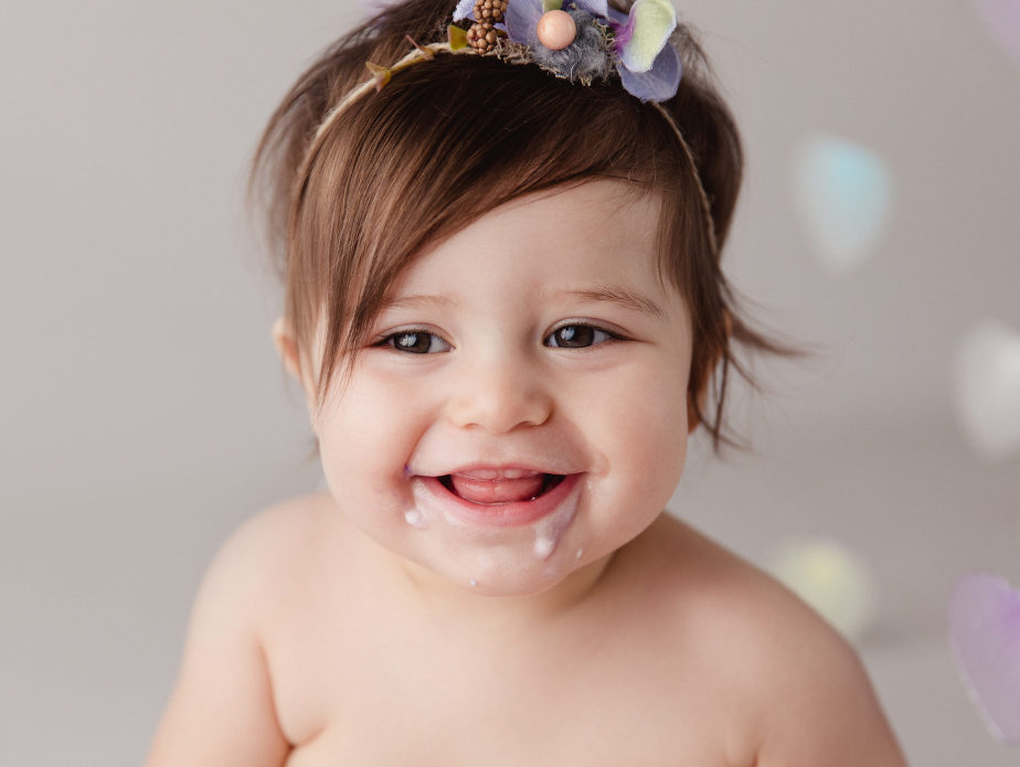 Baby girl makes a mess of her one year birthday cake during her milestone portrait session photographed by Massart Photography RI