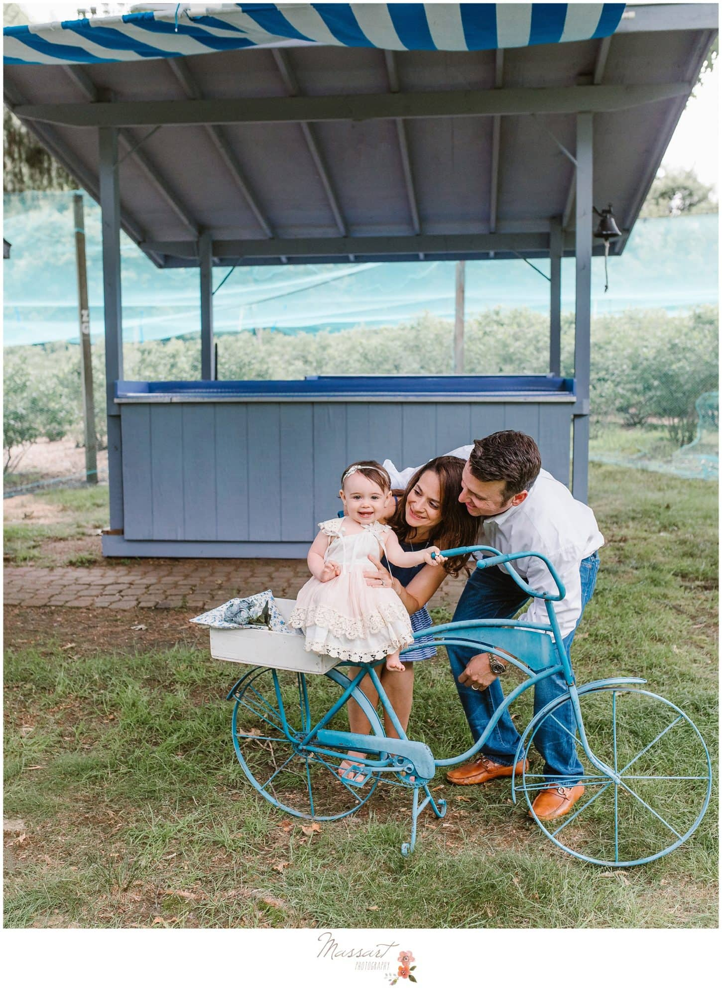 family stands near rustic blue bicycle on the blueberry farm photographed by Massart Photography Rhode Island