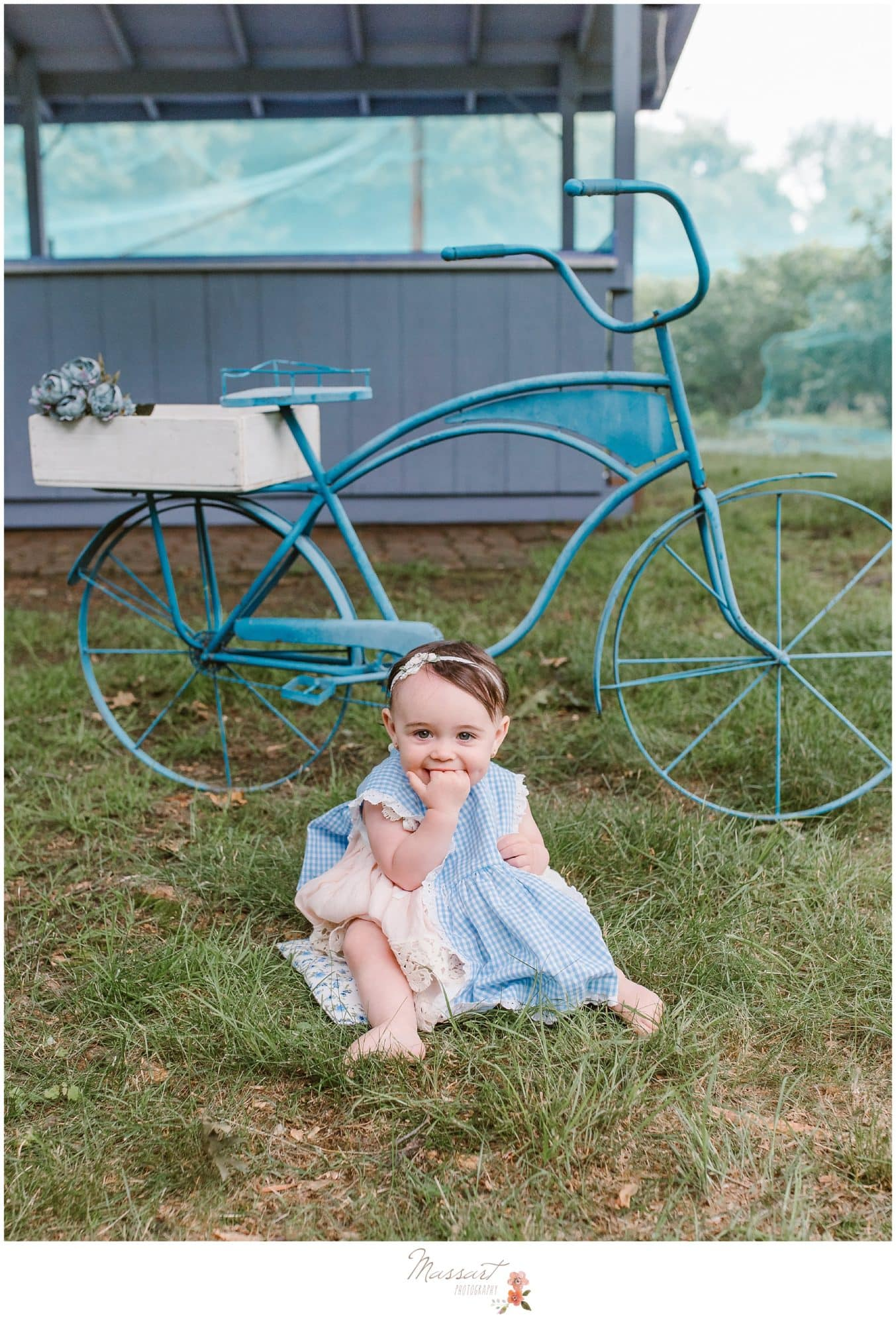 Baby girl sits in front of rustic bicycle during milestone portrait session photographed by Massart Photography RI