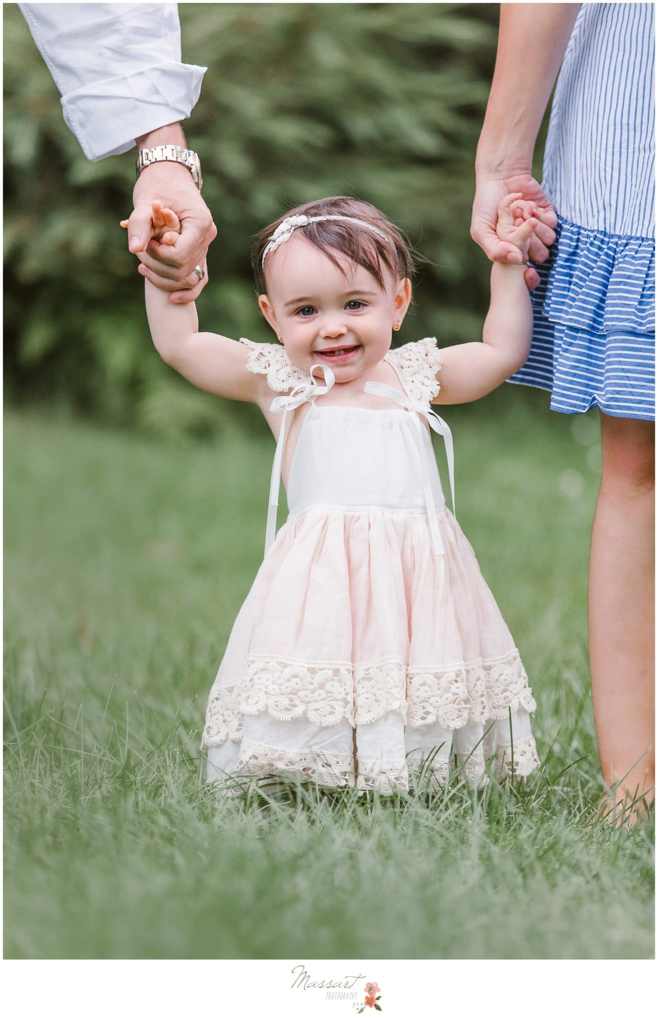 Baby girl holds parent's hands during her one year milestone portrait session photographed by Massart Photography RI