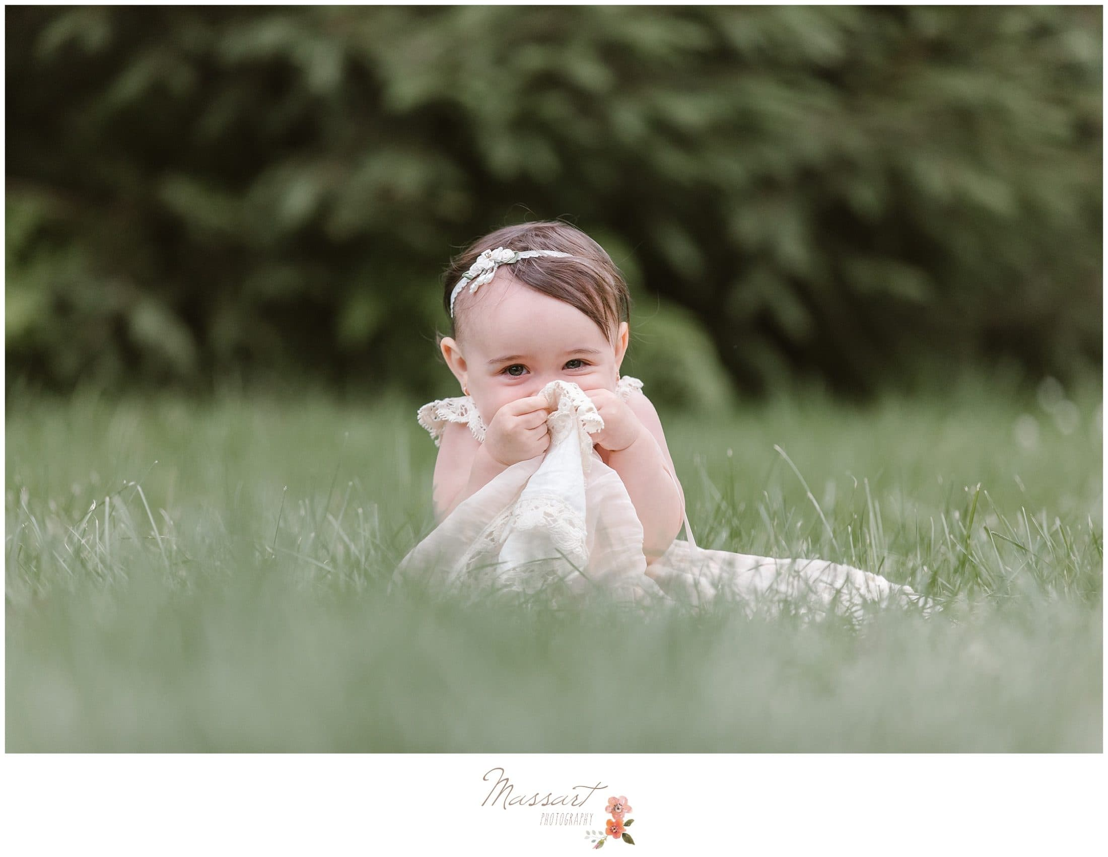 one year old baby girl sits in grass at the blueberry farm during her milestone cake smash photographed by Massart Photography Rhode Island
