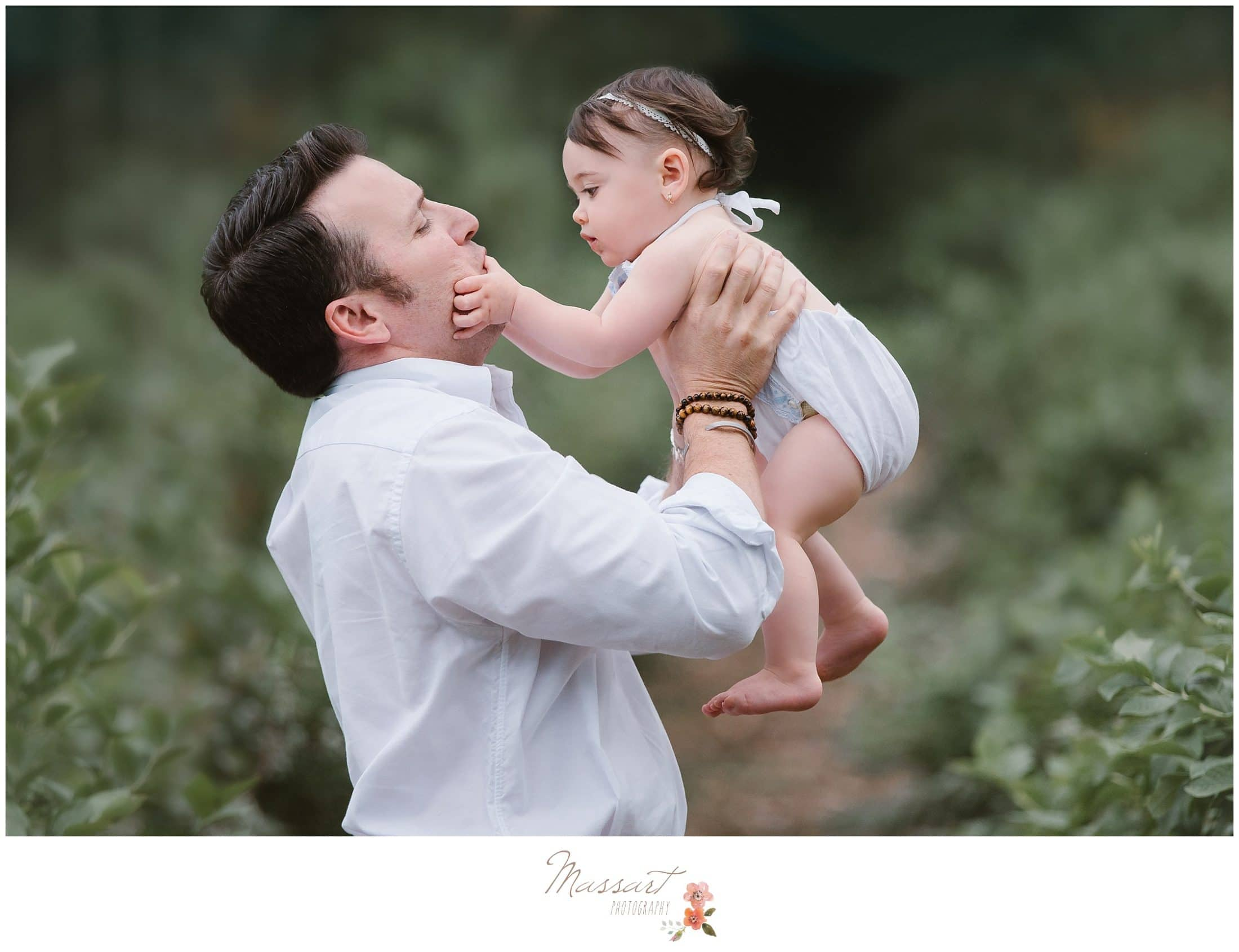 father and daughter playing in the blueberry farm during one year milestone cake smash photographed by Massart Photography Rhode Island