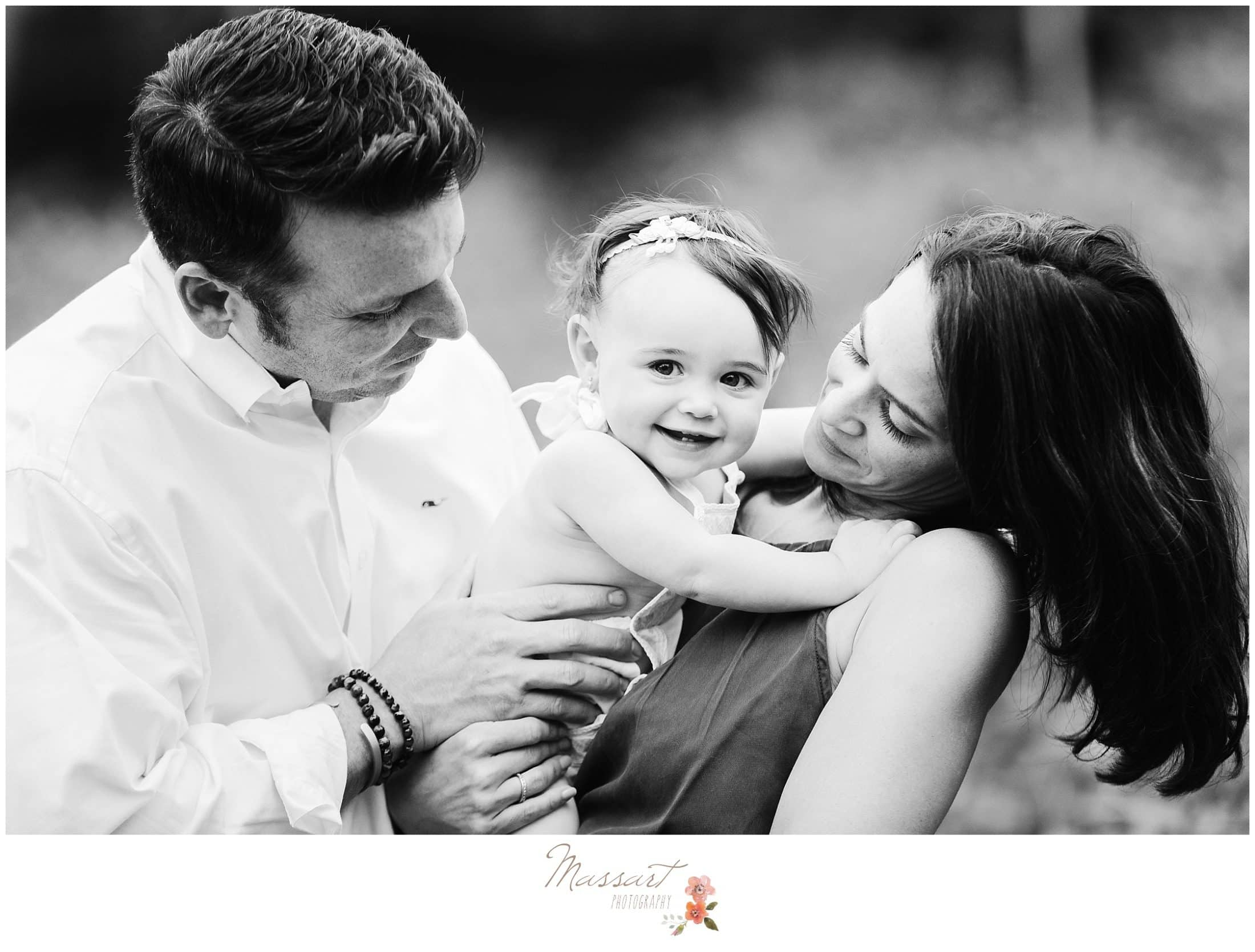 Black and white image of mother, father and one year old daughter during milestone cake smash session photographed by Massart Photography RI