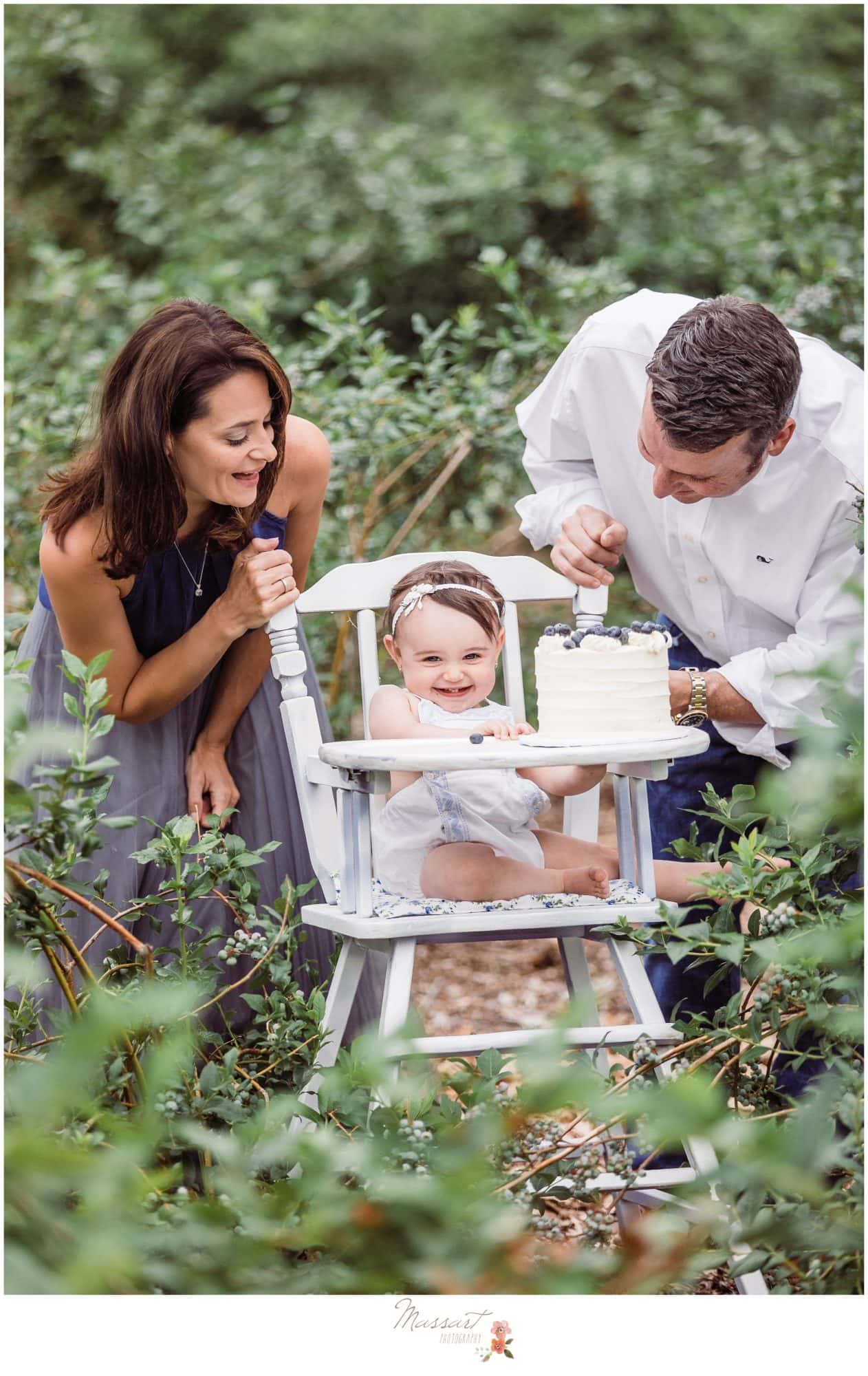 Mom and dad sing happy birthday to baby girl during her blueberry farm cake smash session photographed by Massart Photography Rhode Island