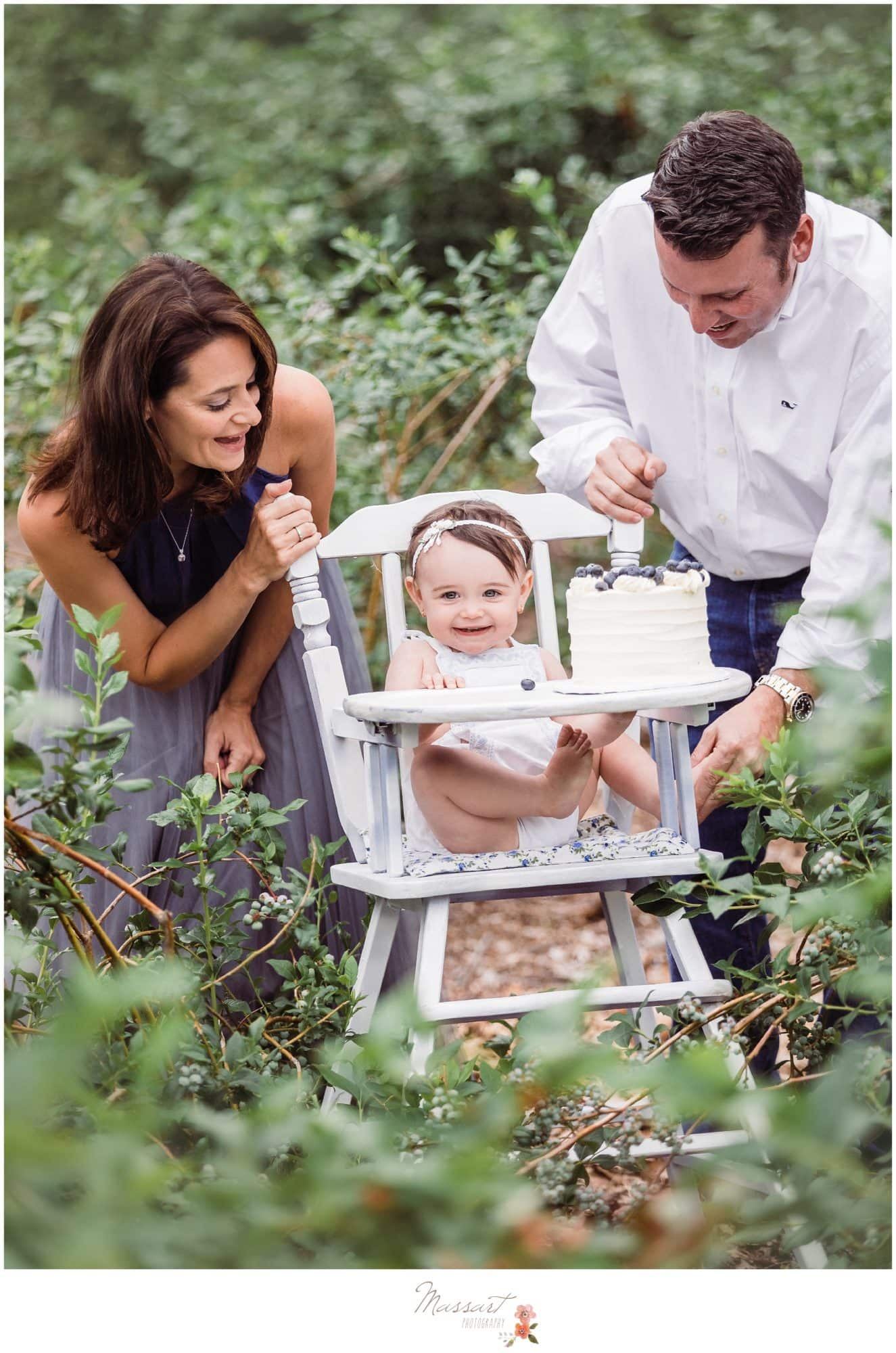 Baby girl in a white high chair with her mom and dad during her blueberry farm cake smash session photographed by Massart Photography Rhode Island