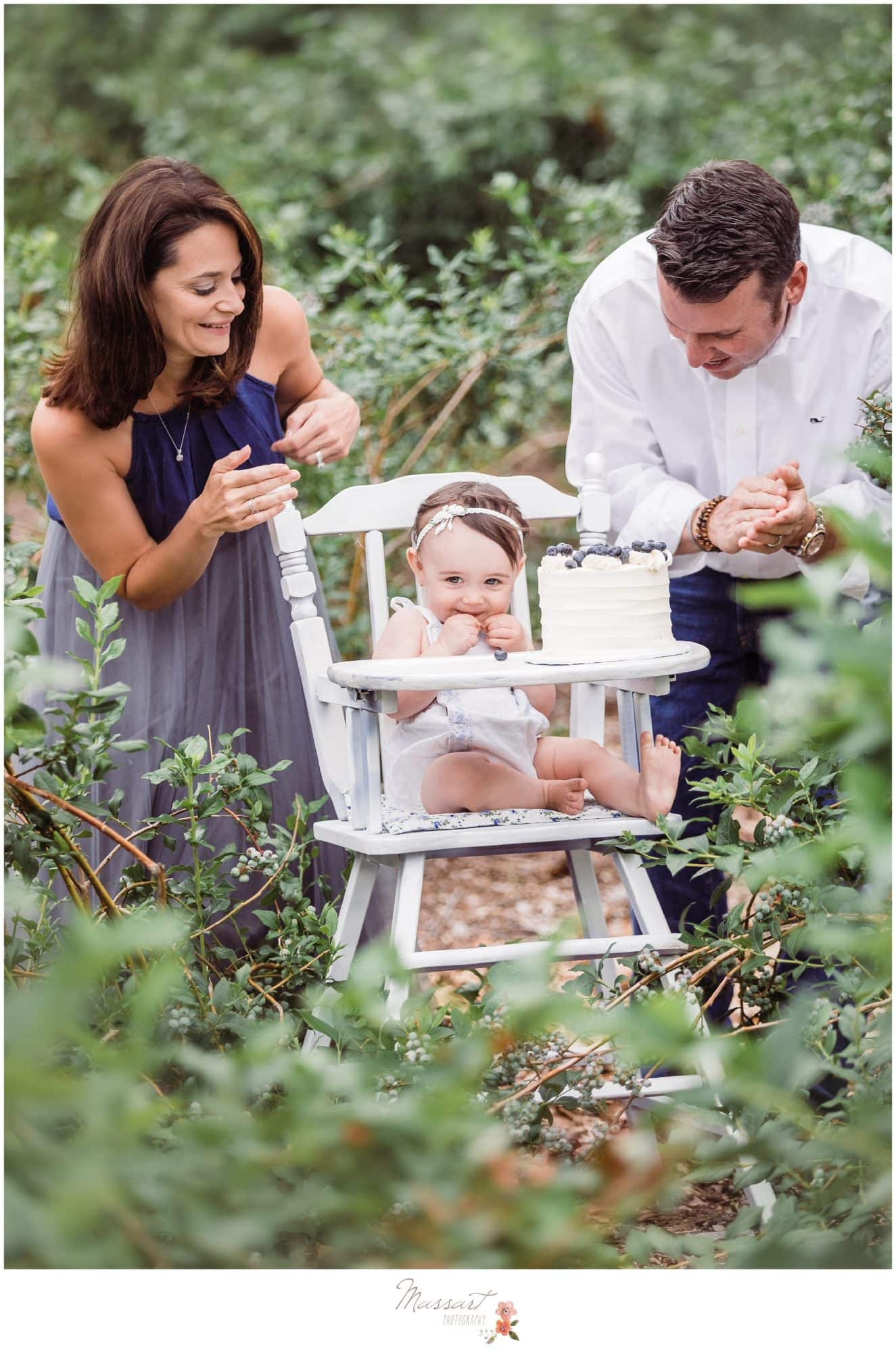 Mom and dad watch as baby girl eats her blueberry farm cake during her milestone cake smash session photographed by Massart Photography Rhode Island