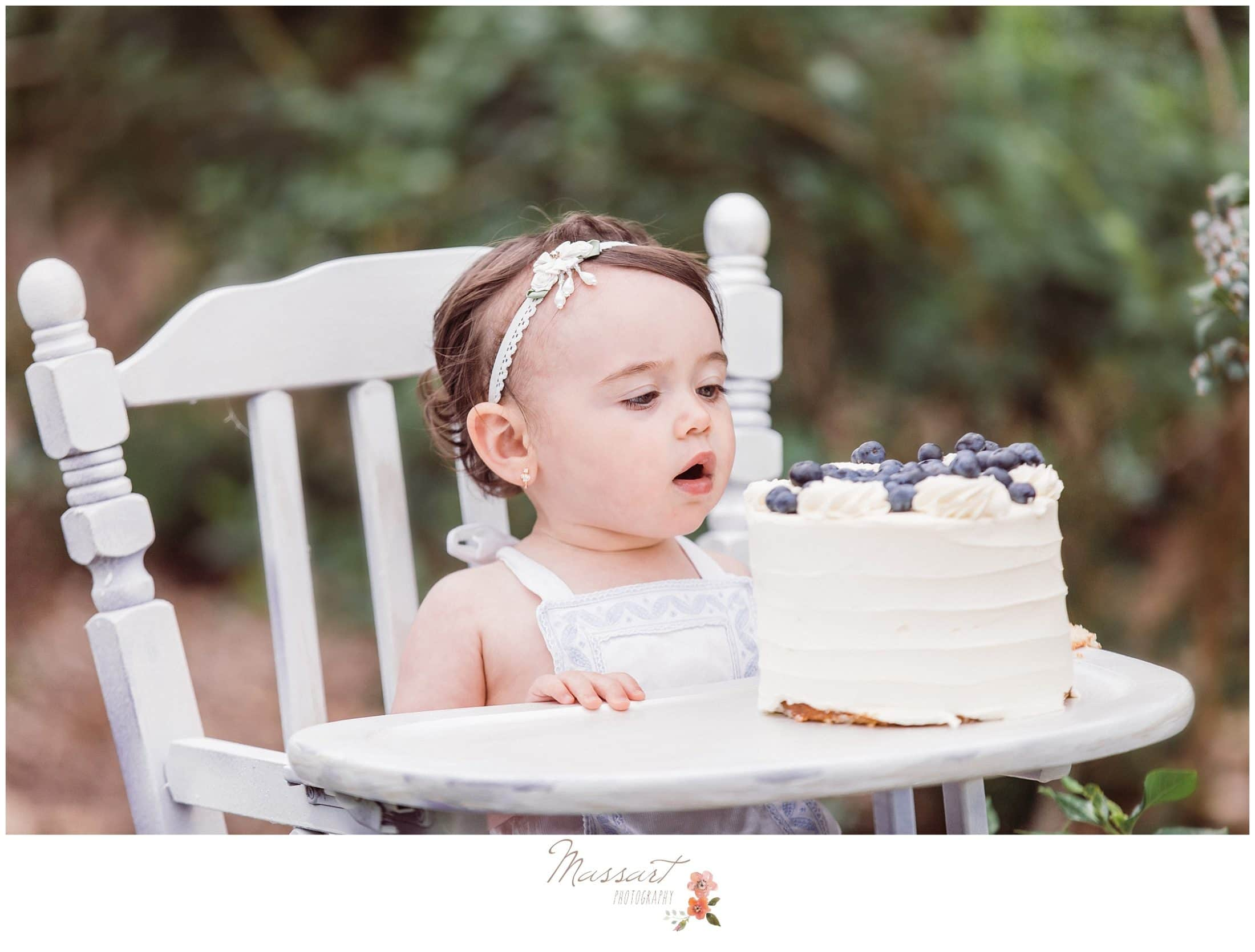 Baby looks at her blueberry cake during her blueberry farm cake smash session photographed by Massart Photography RI