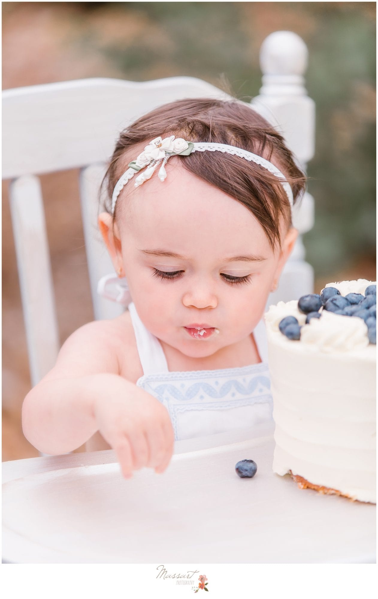 Baby girl eats her blueberry cake during her milestone cake smash session photographed by Massart Photography Rhode Island