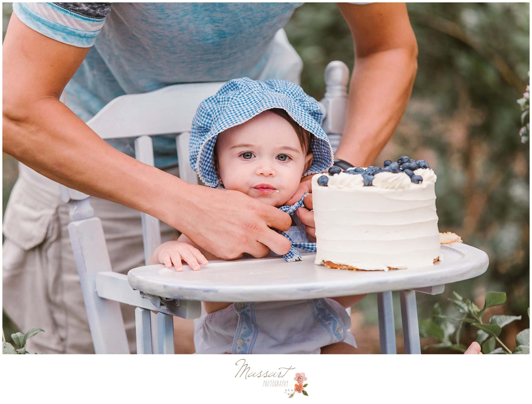 Baby wears a blue hat during her cake smash session at the blueberry farm photographed by Massart Photography RI