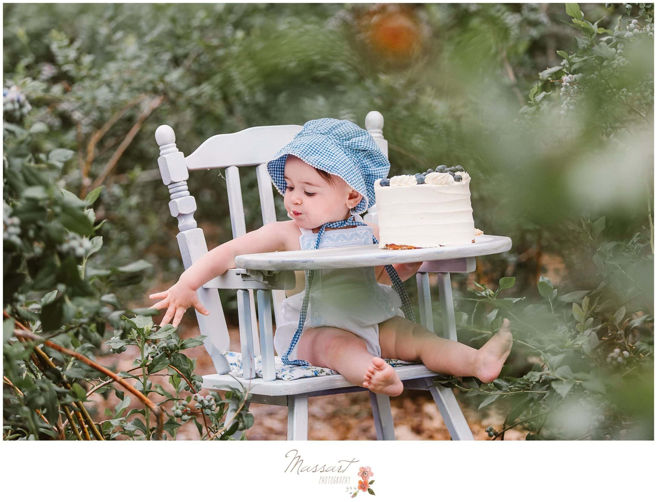 Baby girl in a blue hat sits in her white high chair eating her blueberry cake during her cake smash session photographed by Massart Photography Rhode Island