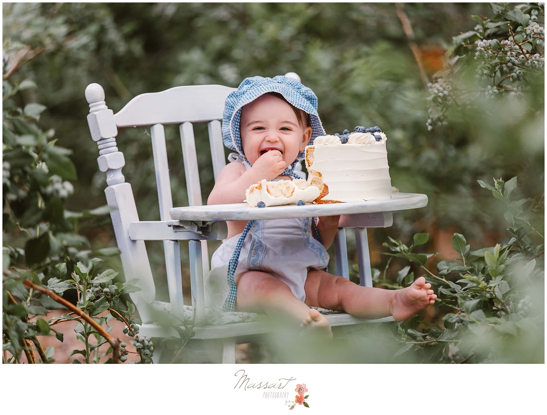 Baby girl laughs while smashing her blueberry cake during her milestone session photographed by Massart Photography RI