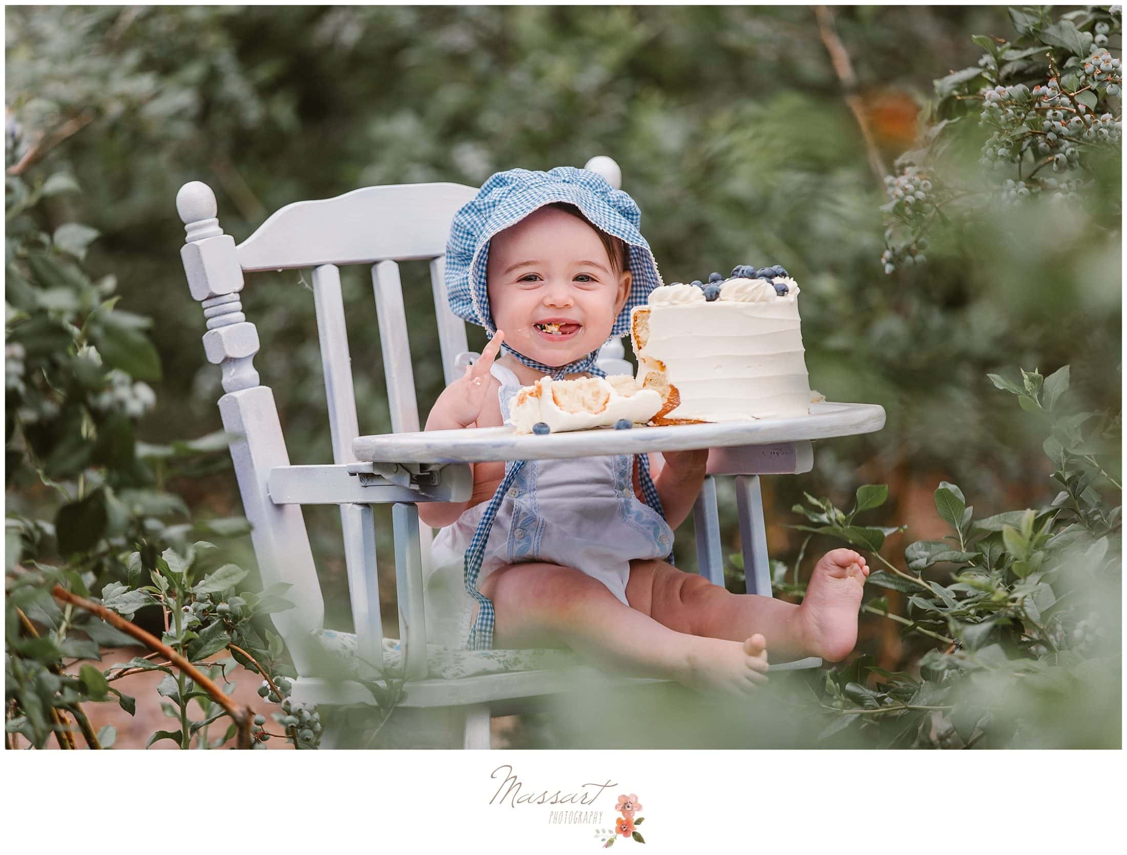 Baby girl sits in white high chair and eats her blueberry cake during her cake smash session photographed by Massart Photography Rhode Island