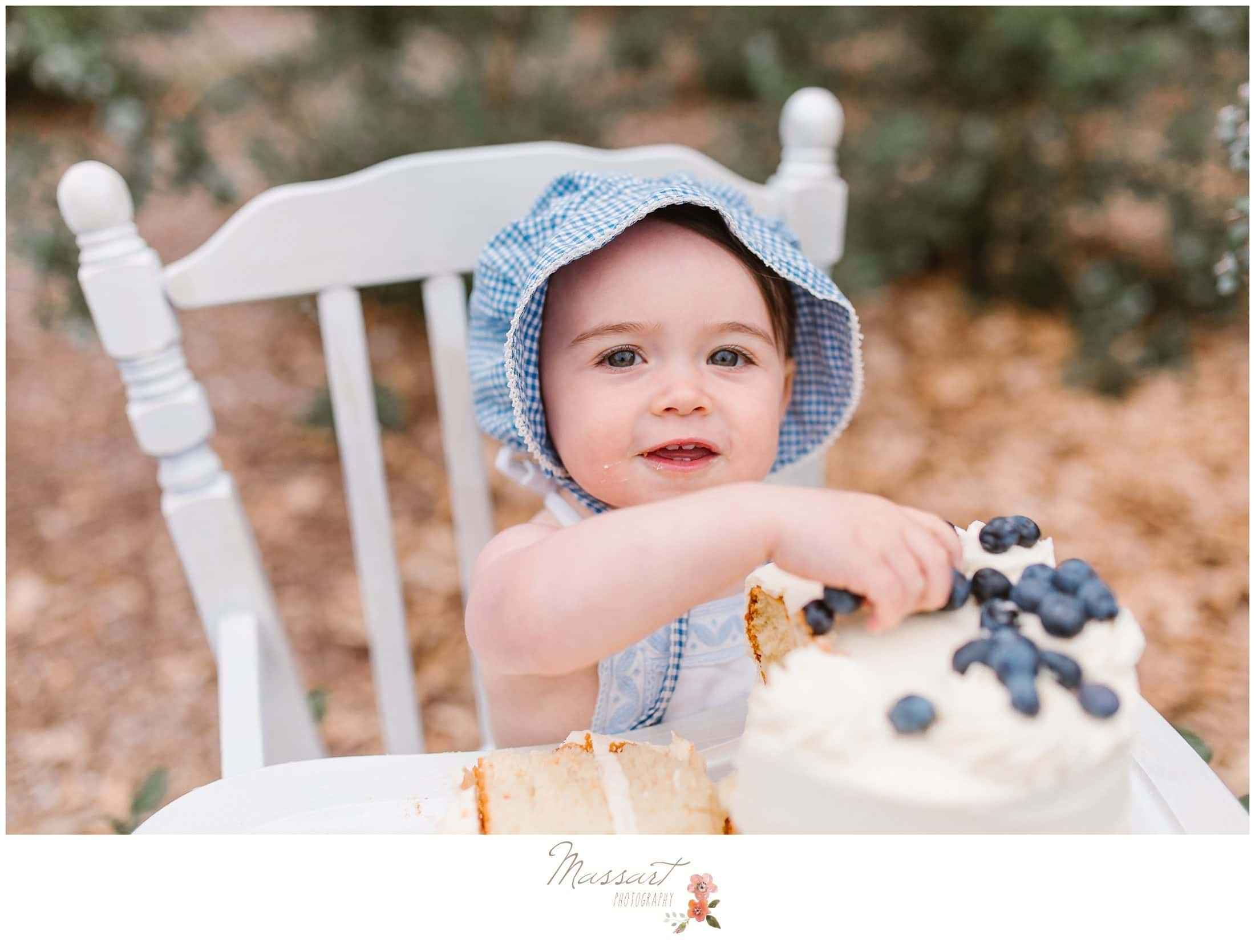 Baby smashes her blueberry cake at the blueberry farm during her cake smash session photographed by Massart Photography Rhode Island